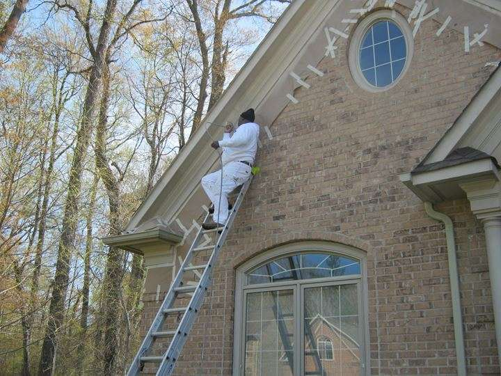 Spray painting exterior eaves on a beautiful home